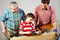 a boy working with plane under his father and grandpa's supervision - stock photo