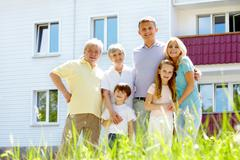 Portrait of happy senior and young couples standing outdoors with new cottage at Stock Photos