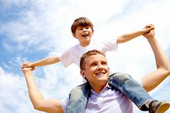 portrait of happy man holding his son on neck on the background of sky - stock photo