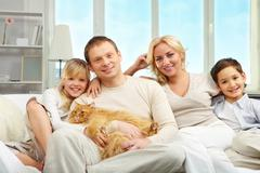 A young family with son and daughter sitting on sofa, looking at camera and smil Stock Photos
