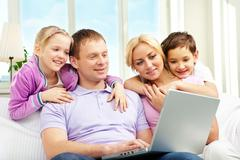 A family of four sitting on sofa and looking at laptop screen Stock Photos