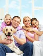 A young family of four with a dog sitting on sofa, looking at camera and smiling Stock Photos