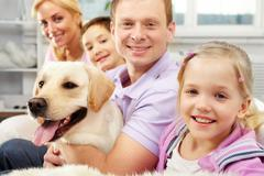 a happy family of four with a dog sitting on sofa, the focus is on the daughter - stock photo