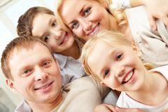 close-up of a smiling family of four - stock photo