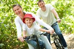 Portrait of happy woman with son riding a bicycle in park on background of male Stock Photos