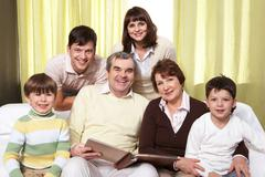 Portrait of happy family of six sitting on sofa and looking at camera Stock Photos