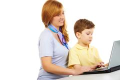 Portrait of woman teaching to type young boy Stock Photos