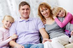 portrait of happy family sitting on the sofa together - stock photo