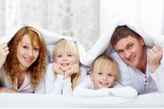 Portrait of cheerful family with twins lying under blanket Stock Photos