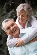 Portrait of a happy senior woman embracing her husband Stock Photos