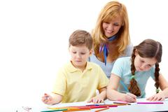 Portrait of children drawing pictures and teacher standing near Stock Photos