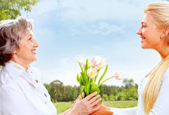 portrait of young woman giving tulips to her mother - stock photo