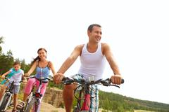 sportive man on bike in front of his wife and son - stock photo