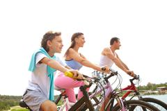 a family of three cycling together - stock photo