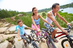 portrait of family of three with bikes on a rock - stock photo