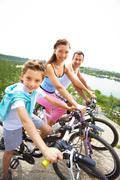 Portrait of happy family riding bikes in summer Stock Photos