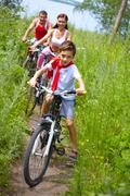 little boy riding bike with his parents - stock photo