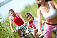 a little boy sitting on bike between mother and father - stock photo
