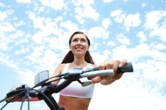 portrait of a woman sitting on bike - stock photo