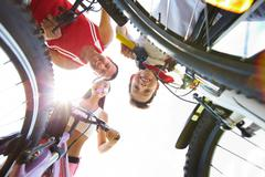 below view of family of three on bikes looking at camera - stock photo