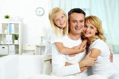 portrait of happy parents with their daughter looking at camera at home - stock photo