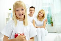 portrait of happy daughter with giftbox looking at camera with parents on backgr - stock photo