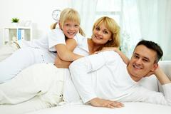 portrait of happy parents with their daughter having rest at home - stock photo