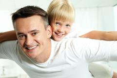 Portrait of happy father holding daughter on back and both looking at camera Stock Photos