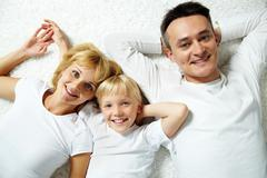 Portrait of cheerful family in casual clothes looking at camera Stock Photos