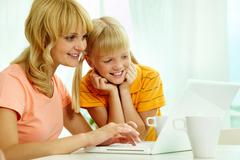 Image of happy mother and daughter using home internet Kuvituskuvat