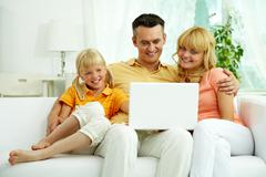 Image of friendly family sitting on the sofa and looking at laptop Stock Photos