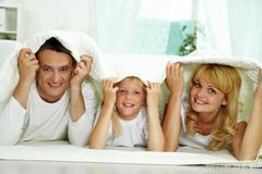 portrait of happy parents and their daughter with blanket above their heads - stock photo