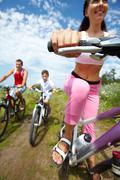 Family of three cycling outdoors Stock Photos