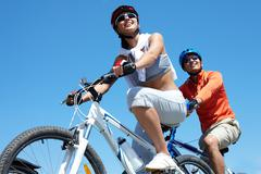 a young couple racing on bicycles against blue sky - stock photo