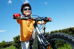 Portrait of happy child on bicycle against blue sky Stock Photos