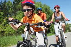 Portrait of happy boy riding bicycle in the park with his parents behind Stock Photos