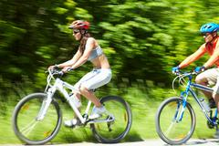 Image in motion of two bicyclists riding on country road Stock Photos
