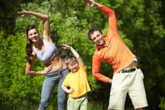 Portrait of family of three doing physical exercise in park Stock Photos