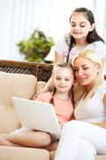 pretty woman and her two daughters sitting on sofa and looking at laptop screen - stock photo