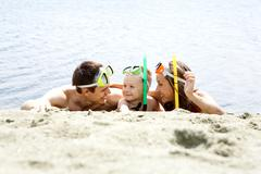Portrait of cheerful couple and their son in diving equipment lying on sandy sho Stock Photos