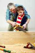 A grandfather teaching a boy to work with saw Stock Photos