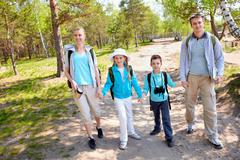 Portrait of family members going down country road in summer Stock Photos