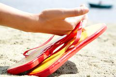 Image of female hand holding flip flops over sandy shore Stock Photos