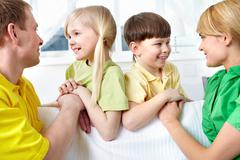 A young family of four looking at each other and smiling Stock Photos