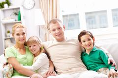 A young family of four sitting on sofa, looking at camera and smiling Stock Photos