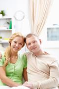 a young couple sitting on sofa and looking at camera - stock photo