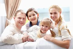 A young family of four looking at camera and smiling Stock Photos