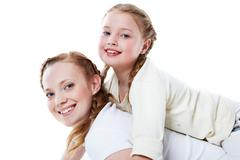 Joyful toddler on back of her mother Stock Photos