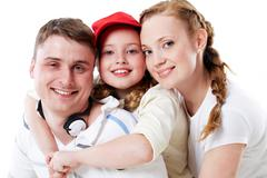 portrait of happy parents and their daughter in studio - stock photo