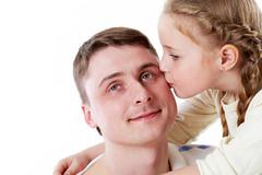 Cute girl kissing her father Stock Photos